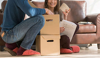Casal empacotando os pertences para fazer mudança