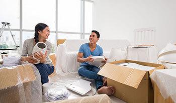Casal conversando enquanto fazem a embalagem dos móveis para mudança