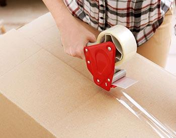 Pessoa lacrando uma caixa e fazendo a embalagem de Móveis