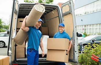 Homens carregando um tapete e uma caixa de papelão durante a mudança de apartamento